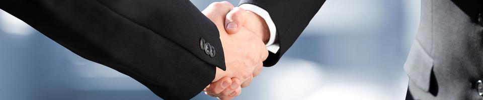 2 Geschäftsmenschen schütteln sich die Hände im Anzug